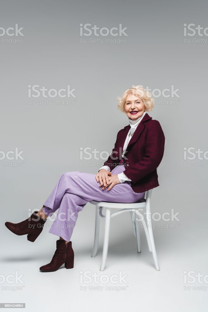 smiling senior woman sitting on chair and looking at camera on grey zbiór zdjęć royalty-free