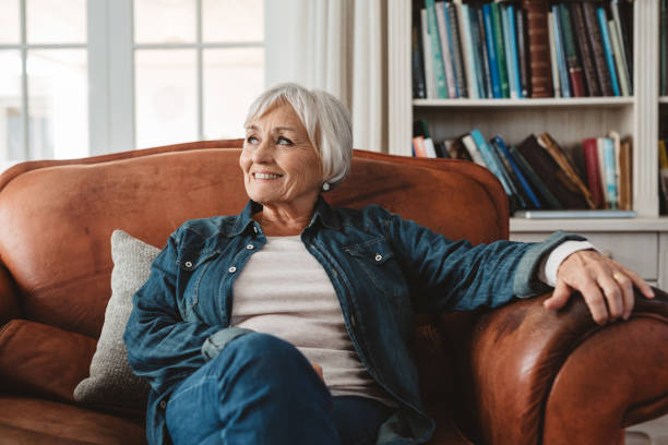 Smiling senior woman sitting on her sofa at home stock photo