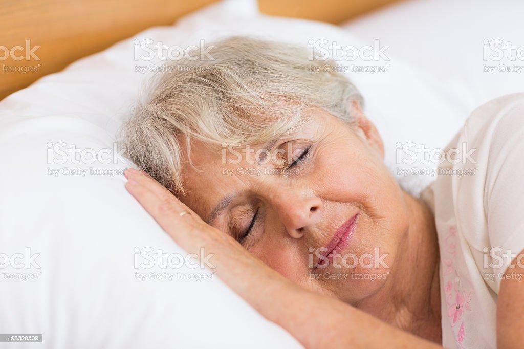 Smiling senior woman sleeping stock photo