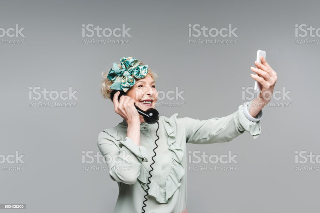 smiling senior woman taking selfie while talking by vintage phone isolated on grey royalty-free stock photo