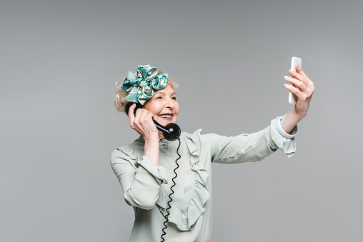 Smiling Senior Woman Taking Selfie While Talking By Vintage Phone Isolated On Grey Stock Photo - Download Image Now
