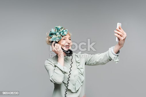 Smiling Senior Woman Taking Selfie While Talking By Vintage Phone Isolated On Grey Stock Photo & More Pictures of Adults Only