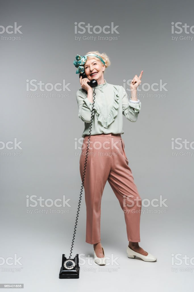 smiling senior woman talking by vintage phone and pointing up on grey royalty-free stock photo