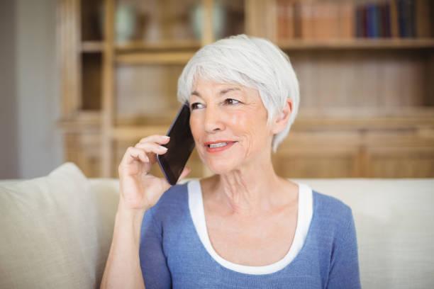 Smiling senior woman talking on mobile phone in living room Smiling senior woman talking on mobile phone in living room at home 65 69 years stock pictures, royalty-free photos & images