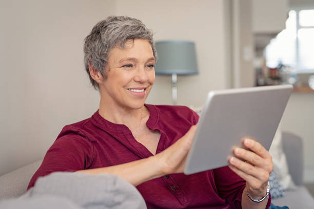 Smiling senior woman using digital tablet Smiling senior woman looking her digital tablet while sitting on sofa. Portrait of mature happy woman relaxing at home with digital tablet. Happy lady with gray hair browsing on laptop in living room. 60 64 years stock pictures, royalty-free photos & images