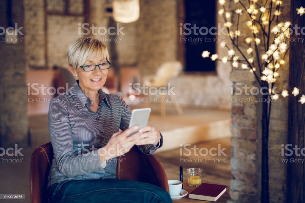 Smiling senior woman using mobile phone in living room stock photo