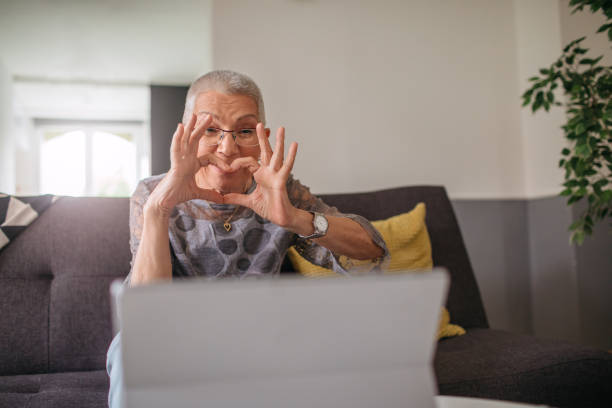 Smiling Senior Woman Using Tablet At Home