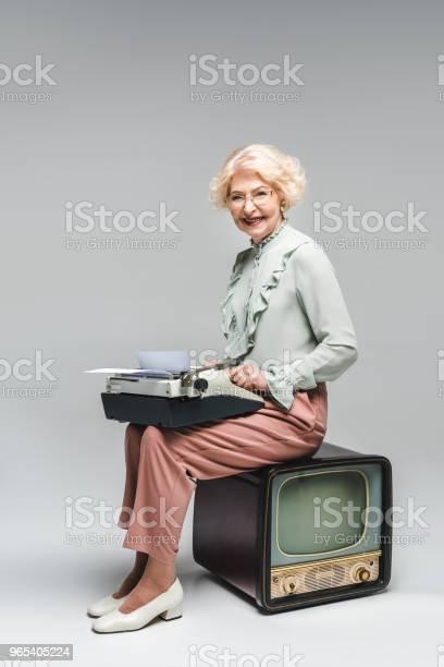 Uśmiechnięta Starsza Kobieta Używająca Maszyny Do Pisania Siedząc Na Vintage Tv Na Szarym - zdjęcia stockowe i więcej obrazów Telewizor