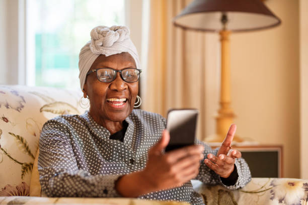Smiling senior woman video calling on her phone while sitting at home stock photo