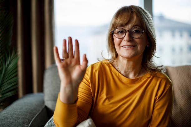 Smiling senior woman waving while looking at camera at home stock photo