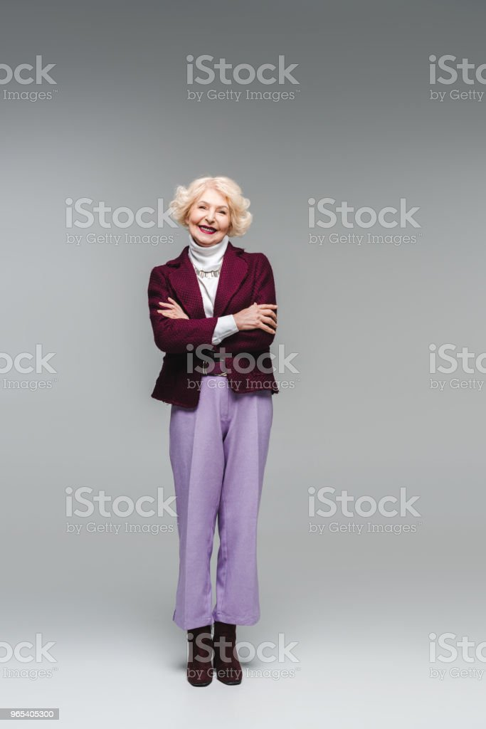smiling senior woman with crossed arms in stylish clothes looking at camera on grey royalty-free stock photo