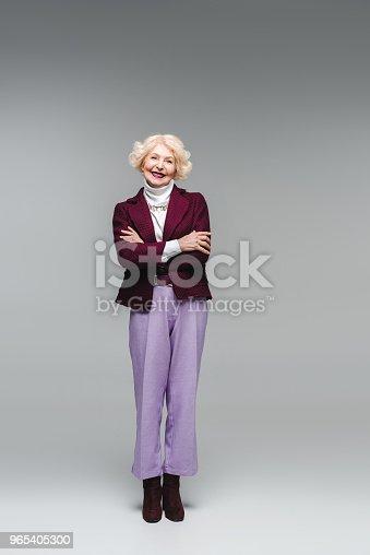 Smiling Senior Woman With Crossed Arms In Stylish Clothes Looking At Camera On Grey - Stockowe zdjęcia i więcej obrazów Elegancja