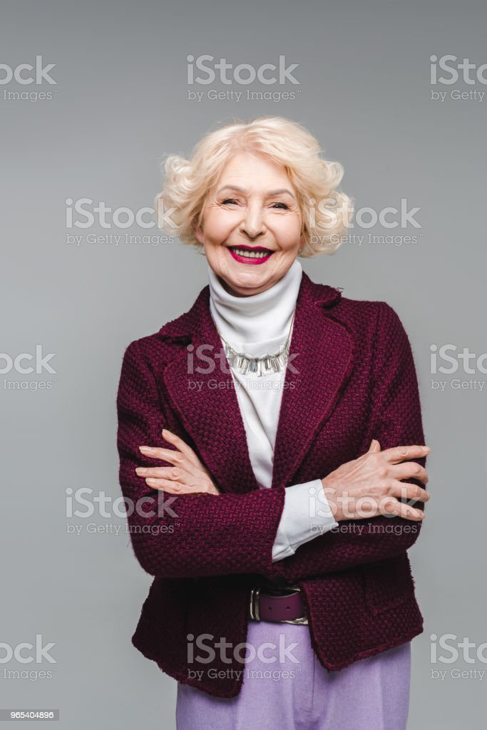 smiling senior woman with crossed arms isolated on grey royalty-free stock photo