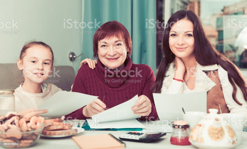 Smiling senior woman with family writing papers - Royalty-free Adult Stock Photo