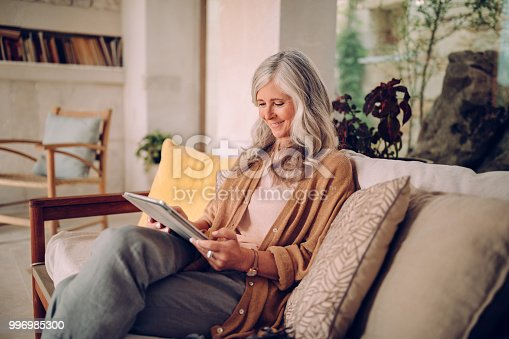 Happy mature woman relaxing on living room sofa and surfing the net using tablet