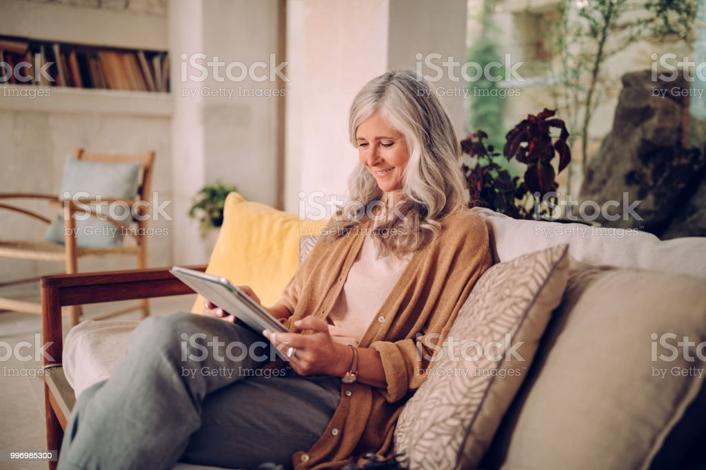 Smiling senior woman with gray hair using tablet at home stock photo