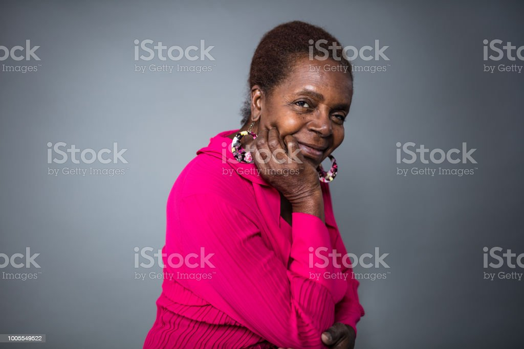 Smiling senior woman with hand on chin stock photo