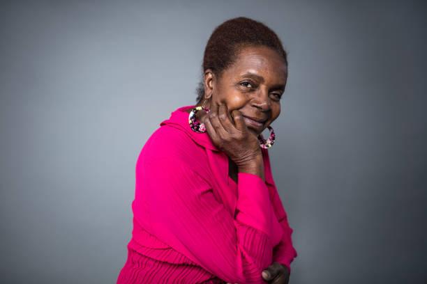 smiling senior woman with hand on chin - mano sul mento foto e immagini stock