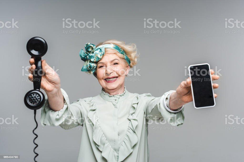 femme senior souriante vintage phone et smartphone en mains isolés sur fond gris - Photo de A la mode libre de droits