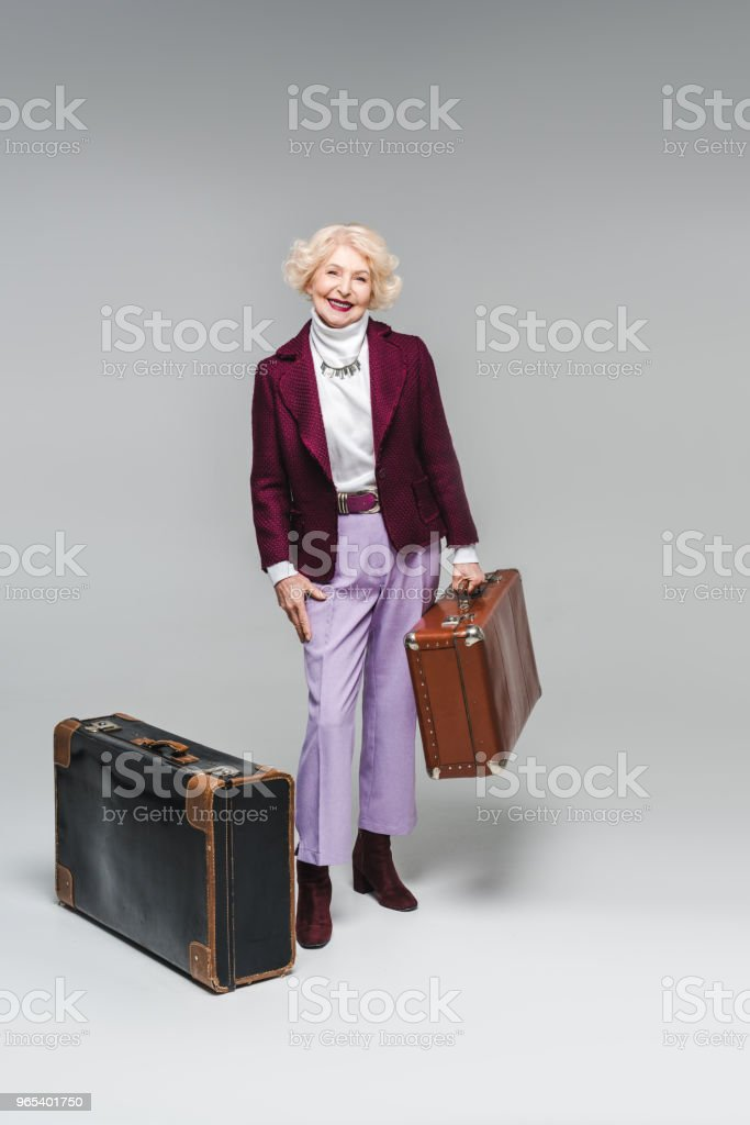 smiling senior woman with vintage suitcases on grey royalty-free stock photo