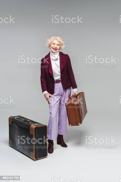 Foto de Sorrindo Mulher Sênior Com Malas Vintage Em Cinza e mais fotos de stock de Adulto