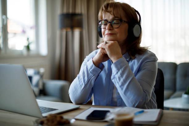 Smiling senior woman with wireless headphones enjoying music at home stock photo