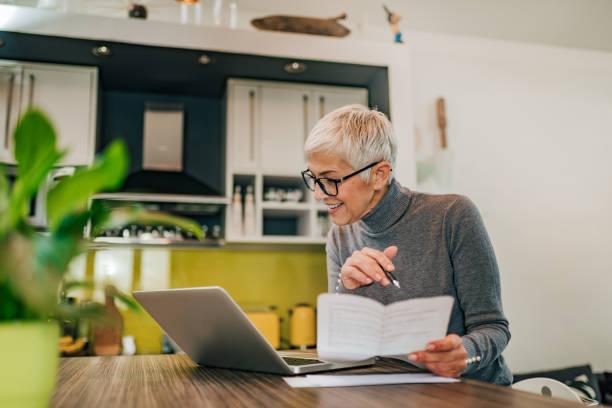 Mujer mayor sonriente trabajando con documentos y computadora portátil en la cocina en la casa moderna. - foto de stock