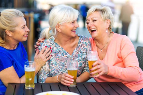 Sourire des femmes âgées ayant une bière dans un pub en plein air - Photo