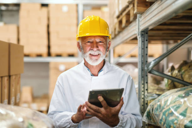 smiling senior worker in uniform and with yellow helmet on head holding tablet and looking at camera while standing in storage. - pensionati lavoratori foto e immagini stock
