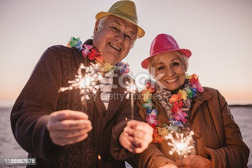 Portrait of a smiling senior couple dressed in party hats and holding sparklers while celebrating New Year's Eve together at the beach at sunset