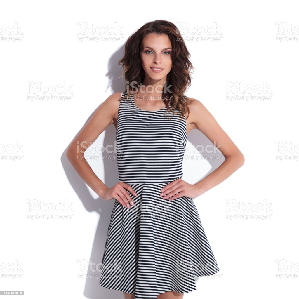 cddb318aa029 smiling sexy woman wearing a cute sundress holding her hips foto stock  royalty-free
