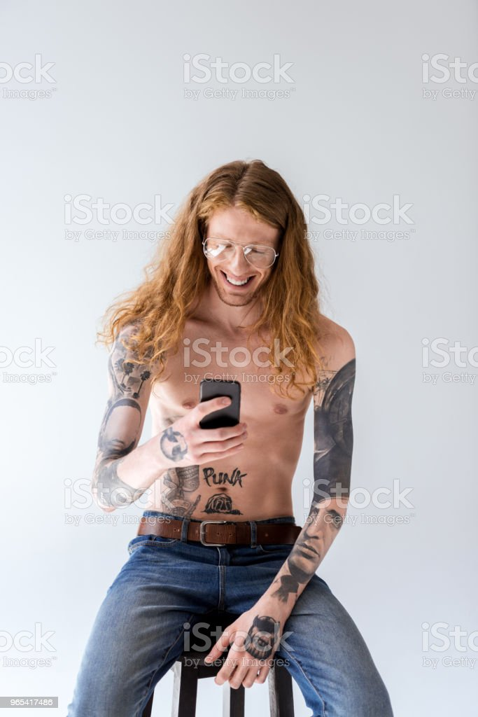 smiling shirtless tattooed man with curly hair looking at smartphone isolated on white zbiór zdjęć royalty-free