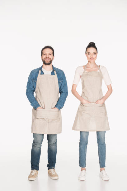 smiling shop assistants in aprons looking at camera isolated on white stock photo