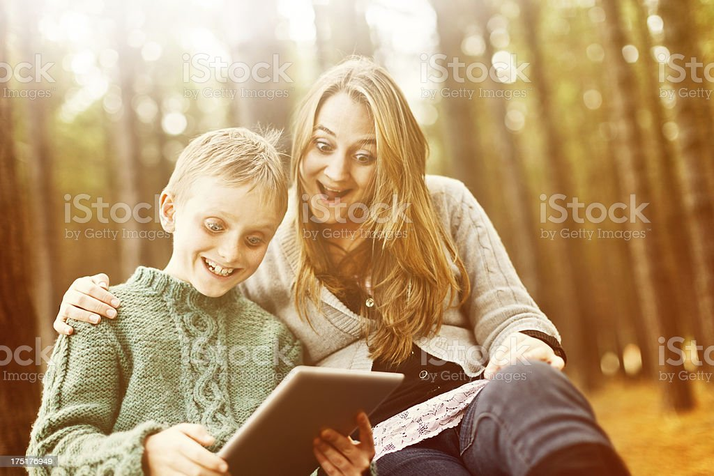 Smiling siblings in forest make amazing discovery on digital tablet stock photo