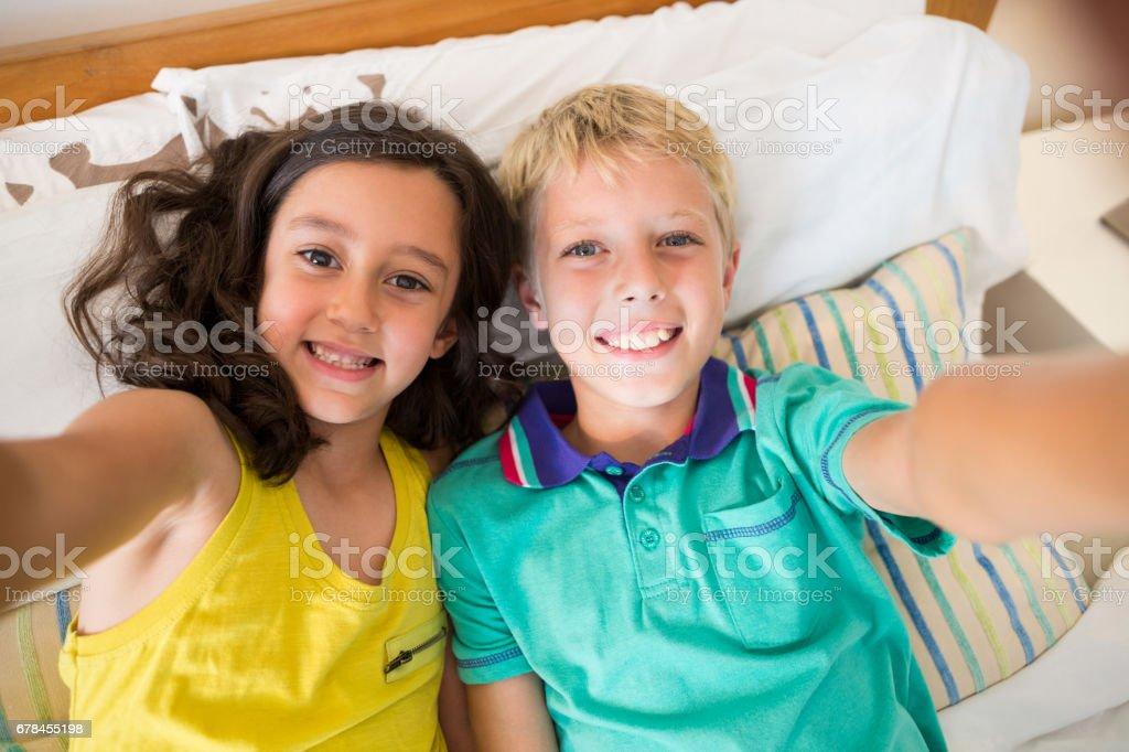 Smiling siblings taking selfie in bedroom royalty-free stock photo