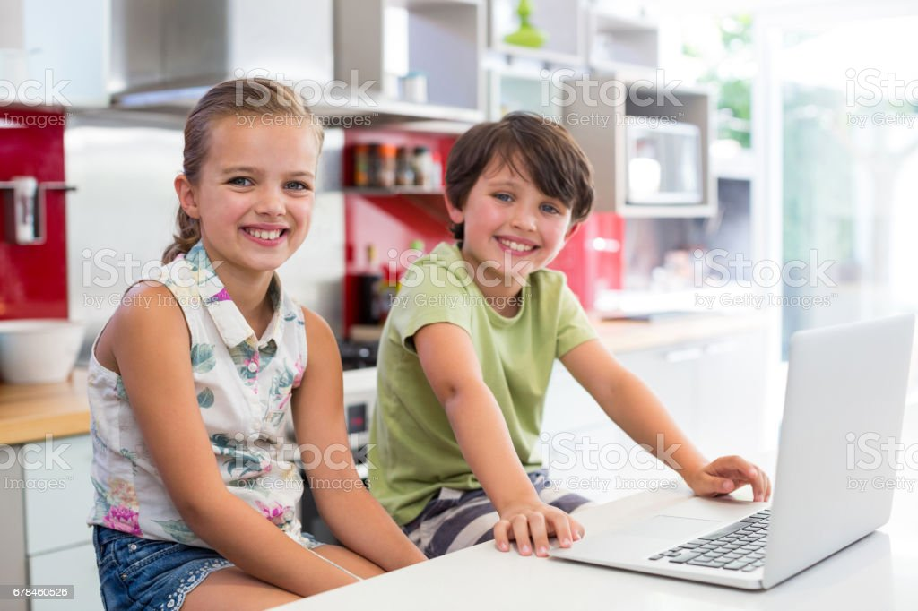 Smiling siblings using laptop in kitchen royalty-free stock photo
