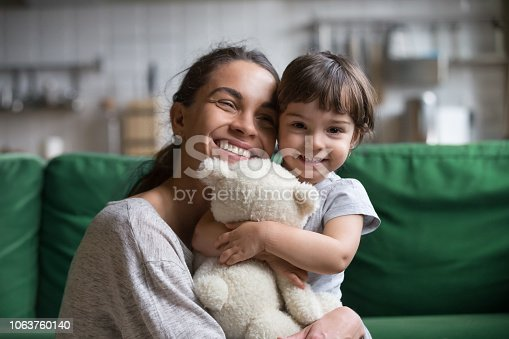 1063760138 istock photo Smiling single young mum embracing little daughter 1063760140