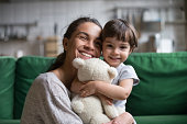 istock Smiling single young mum embracing little daughter 1063760140