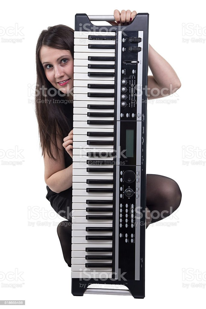 Smiling sitting woman with synthesizer stock photo