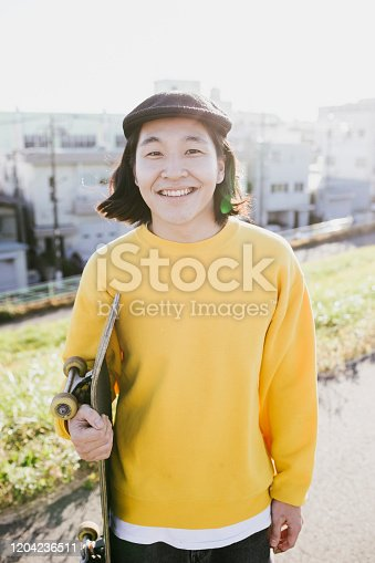 Waist up portrait of a young Japanese skateboarder.