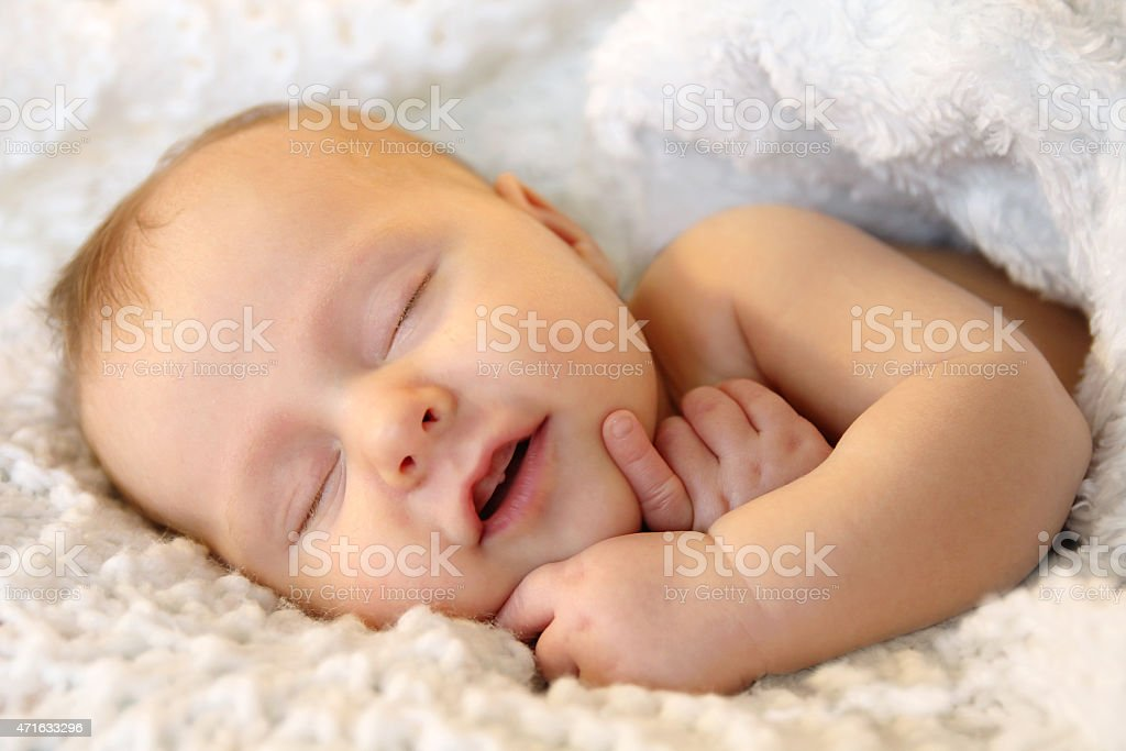 Smiling Sleeping Newborn Baby Girl Wrapped in White Blanket stock photo
