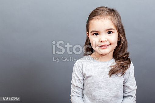 Smiling small girl looking at camera on the grey background