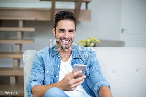 Portrait of smiling smart man using smartphone at home