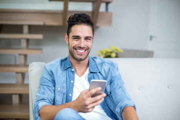 lächelnde kluger mann mit smartphone - 25 29 jahre stock-fotos und bilder