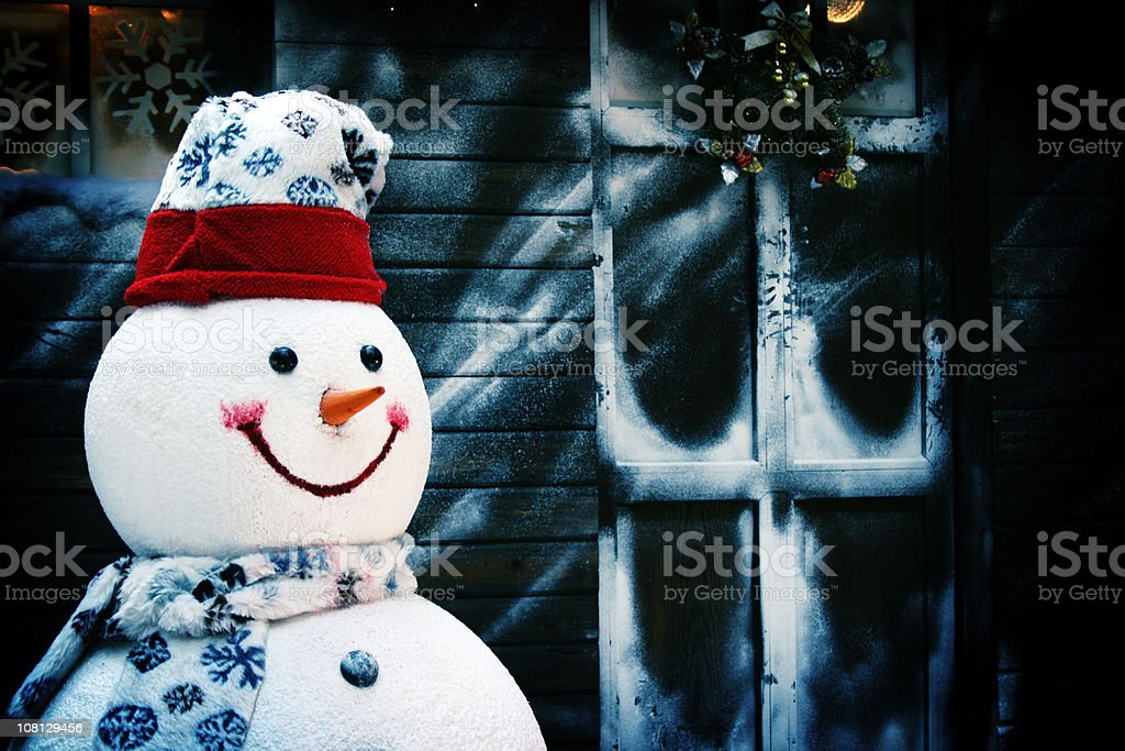 Smiling Snowman in Front of House and Frosty Window royalty-free stock photo