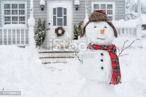 istock Smiling snowman in front of the house on winter day 1277399510