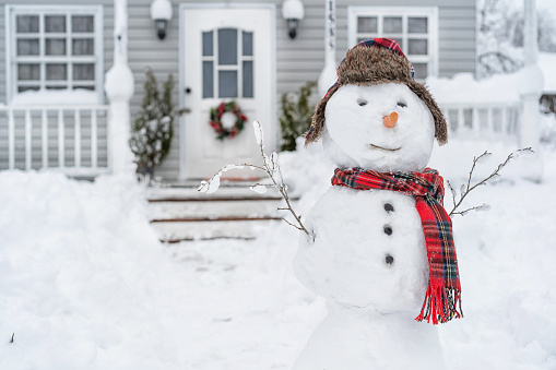 Smiling snowman in front of the house on winter day