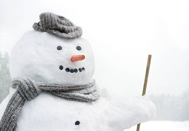 Smiling snowman outdoors in snowfall stock photo