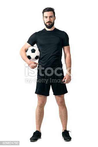 istock Smiling soccer or futsal player wearing black sportswear holding ball 526824792
