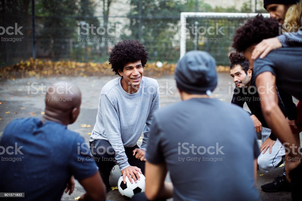 Smiling soccer player planning strategy with team stock photo
